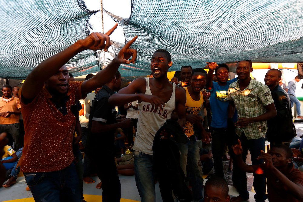 Migrants dance and sing during an impromptu prayer meeting at the stern of the Medecins san Frontiere (MSF) rescue ship Bourbon Argos somewhere between Libya and Sicily at sunset August 8, 2015.  Some 241 mostly West African migrants on the ship are expected to arrive on the Italian island of Sicily on Sunday morning, according to MSF.<br /> REUTERS/Darrin Zammit Lupi <br /> MALTA OUT. NO COMMERCIAL OR EDITORIAL SALES IN MALTA