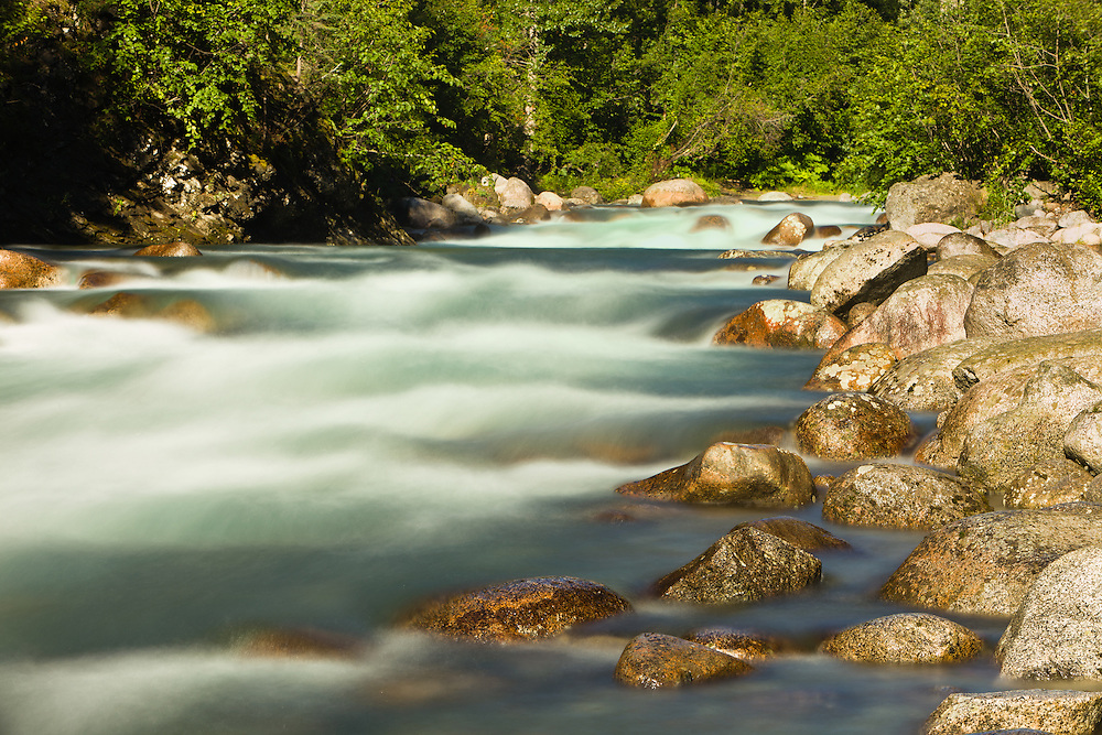 Long exposure of the Little Susitna River flowing through a narrow canyon of boulders at Hatcher Pass in Southcentral Alaska. Summer. Afternoon.
