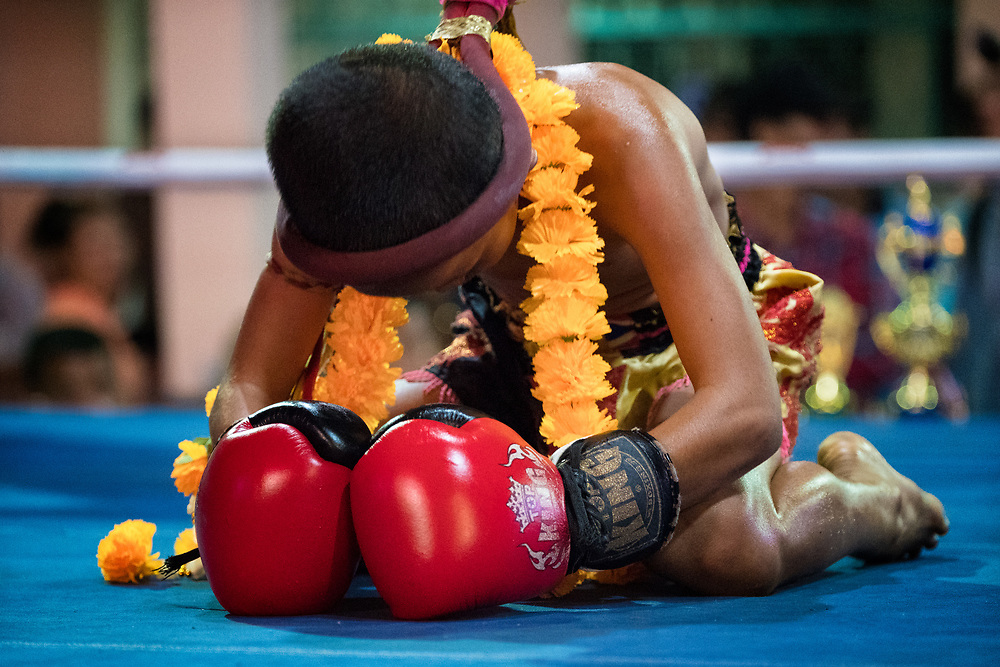 A young Muay Thai fighter prays before a boxing match at a festival in Nakhon Nayok Thailand.