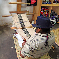 South America, Ecuador, Peguche. A weaver of Peguche demonstrates weaving techniques on his loom and makes a living selling textiles at the Otavalo Market.