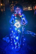 A woman carries her own lighting rig. Dancing in the woods in the early hours of the morning - The 2016 Latitude Festival, Henham Park, Suffolk.