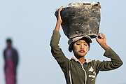 Worker carries rocks to river bank, Ayeyarwady river, Pathein