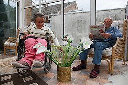 Wheelchair user with Spina Bifida arranging flowers in her conservatory while her father reads a paper.