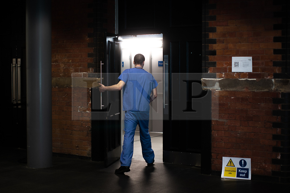© Licensed to London News Pictures . 14/04/2020. Manchester, UK. A clinician enters the hospital from the foyer of the building . The National Health Service has built a 648 bed field hospital for the treatment of Covid-19 patients , at the historical railway station terminus which now forms the main hall of the Manchester Central Convention Centre . The facility is due to open this week (commencing Easter Monday , 13th April 2020 ) and will treat patients from across the North West of England , providing them with general medical care and oxygen therapy after discharge from Intensive Care Units . Photo credit : Joel Goodman/LNP