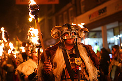 © Licensed to London News Pictures. 04/11/2017. Lewes, UK.A man in viking costume carrying a burning torch as he takes part in celebrations for the traditional Lewes Bonfire Night celebrations on Saturday, 4 November, 2017. Thousands of people attend the parade through the narrow streets of Lewes and burn effigies to celebrate Guy Fawkes nightalso known as bonfire night, the anniversary of the gunpowder plot to blow up the Houses of Parliament in London. Photo credit: London News pictures