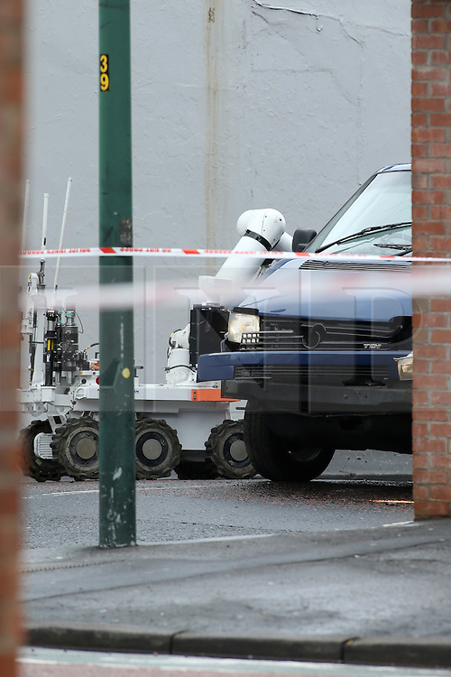 © Licensed to London News Pictures. 4/03/2016. Belfast, Northern Ireland, UK. A British Army Bomb disposal robot approaches a blue van damaged following an early morning explosion in east Belfast. A 52 year old man, who is a serving prison officer, has since died it has been announced today. Photo credit : Paul McErlane/LNP