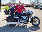 "05 APRIL 2020 - DES MOINES, IOWA:  BYKRMARK CARVER, and his daughter, pray next to Carver's motorcycle during a drive through Palm Sunday service sponsored by Luther Memorial Church on the campus of Grand View University in Des Moines. About 150 people attended the service. They remained in their cars while the ministers read a short passage from the Bible, handed out palms and blessed them. On Sunday, 05 April, Iowa reported 868 confirmed cases of the Novel Coronavirus (SARS-CoV-2) and COVID-19. There have been 22 deaths attributed to COVID-19 in Iowa. Restaurants, bars, movie theaters, places that draw crowds are closed until 30 April. The Governor has not ordered ""shelter in place"" but several Mayors, including the Mayor of Des Moines, have asked residents to stay in their homes for all but essential needs. People are being encouraged to practice ""social distancing"" and many businesses are requiring or encouraging employees to telecommute.        PHOTO BY JACK KURTZ"