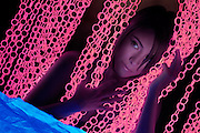 A young woman parts the glowing blinds near her bed.Black light