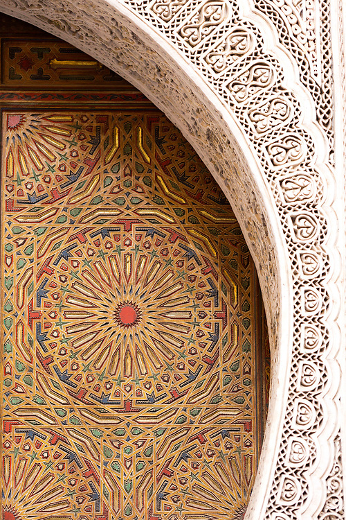 Old Moroccan doorway with intricately carved and painted geomtric patterns and designs, Fez Medina, Morocco, 2015-12-16.<br />