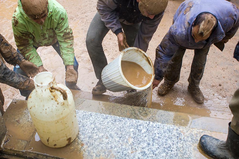 Muslim men making fresh mud, used for the local Ashura ritual. Bijar, Kurdistan Province, Iran.