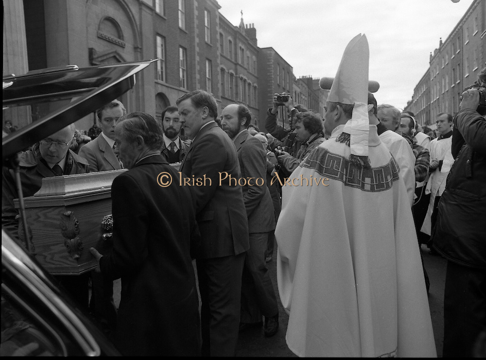 Funeral Of Frank Duff.   (N50)..1980..13.11.1980..11.13.1980..13th November 1980..The Solemn Funeral Mass for Frank Duff, founder of The Legion of Mary,was concelebrated with his Eminence,Cardinal Tómas O'Fiaich,Archbishop of Armagh and Primate of All Ireland as principal celebrant, at St Andrew's Church, Westland Row,Dublin. The funeral took place after the mass to Glasnevin Cemetery..Image of the coffin being borne by Legionaries as it is carried to the waiting hearse. Cardinal O'Fiaich is in the foreground carries out the final blessing.