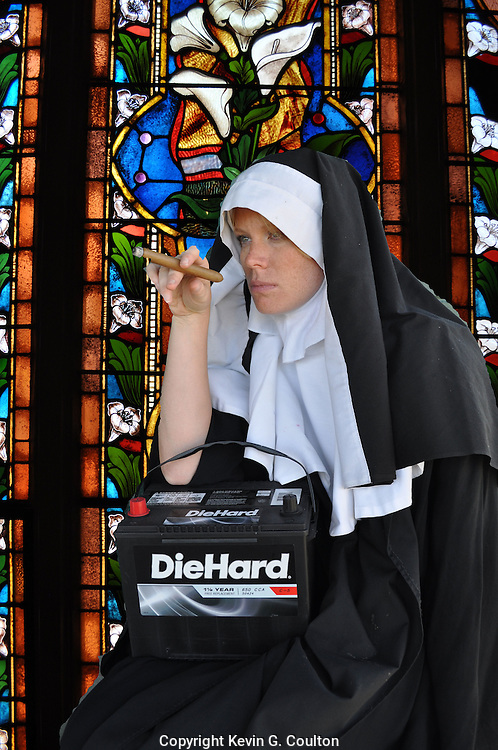 "Humorous photograph of a nun in a habit smoking a cigar in church and holding a Die Hard battery visually depicting the saying ""Bad habits die hard!"""