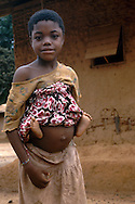 Young girl carrying her baby sibling in a remote village of Mambele, southeast Cameroon.