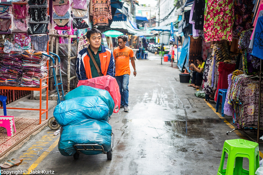 06 JUNE 2013 - BANGKOK, THAILAND:     A porter carries clothes to a wholesale shop in Bobae Market in Bangkok. Bobae Market is a 30 year old famous for fashion wholesale and is now very popular with exporters from around the world. Bobae Tower is next to the market and  advertises itself as having 1,300 stalls under one roof and claims to be the largest garment wholesale center in Thailand.       PHOTO BY JACK KURTZ