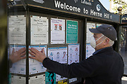 As the UK government considers further restrictions of movement in public places during the Coronavirus pandemic, a member of local community group, the Herne Hill Forum, attaches health guidelines printed off from the BBC, to help south Londoners understand all precautions necessary to keep them virus-free, on 23rd March 2020, in London, England.