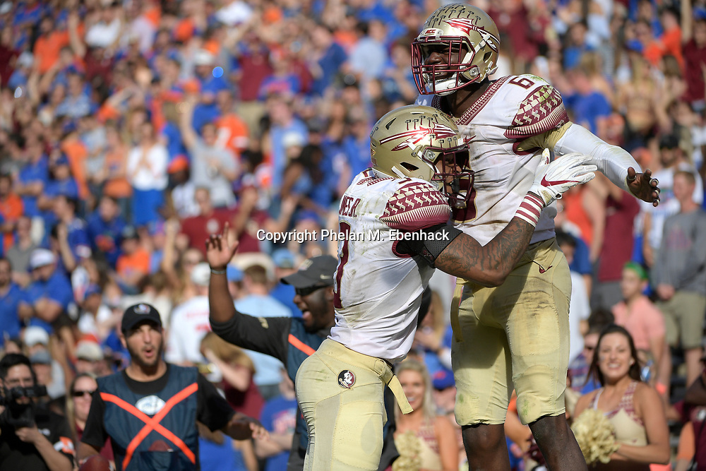 Florida State linebacker Matthew Thomas (6) is congratulated by defensive back Derwin James (3) after intercepting a pass during the second half of an NCAA college football game against Florida Saturday, Nov. 25, 2017, in Gainesville, Fla. FSU won 38-22. (Photo by Phelan M. Ebenhack)