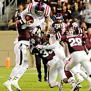 Mississippi quarterback Bo Wallace (14) jumps over Texas A&M defenders for extra yards during the second half of an NCAA college football game in College Station, Texas, Saturday, Oct. 11, 2014. No. 3 Mississippi won 35-20. (Photo/Thomas Graning)