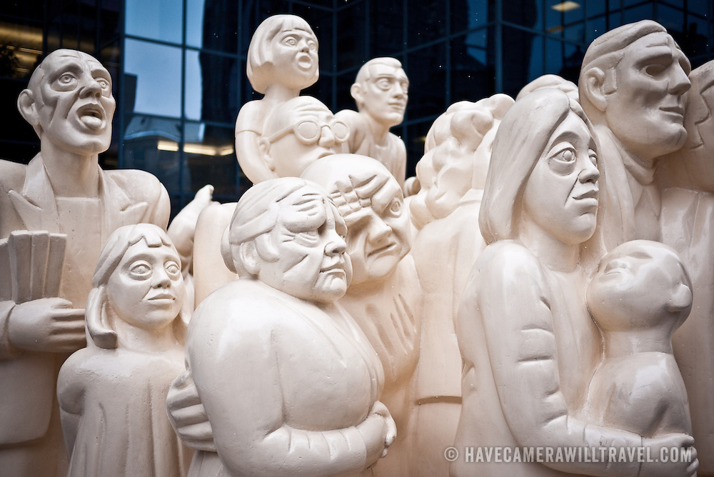 """The Illuminated Crowd"" (1985) by English artist Raymond Mason. Installed outside a large office building in downtown Montreal, the sculpture carries the inscription: ""A crowd has gathered, facing a light, an illumination brought about by a fire, an event, an ideology--or an ideal. The strong light casts shadows, and as the lights toward the back and diminishes, the mood degenerates; rowdiness, disorder and violence occur, showing the fragile nature of man. Illumination, hope, involvement, hilarity, irritation, fear, illness, violence, murder and death--the flow of man's emotion through space."""