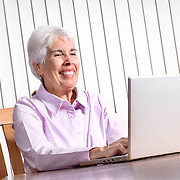 A 65-year-old woman uses a laptop to search the internet and communicate with out-of-state family and friends. Computer literacy is increasing among the Baby Boomers.