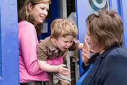 Nanny and little boy on the doorstep saying goodbye to his mother,