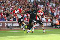 Football - 2017 / 2018 Premier League - Southampton vs. West Ham United<br /> <br /> Michail Antonio of West Ham United rides the challenges from Southampton's Nathan Redmond and Southampton's Steven Davis at St Mary's Stadium Southampton<br /> <br /> COLORSPORT/SHAUN BOGGUST