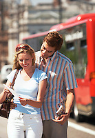 Young vacationing couple on London street reading map