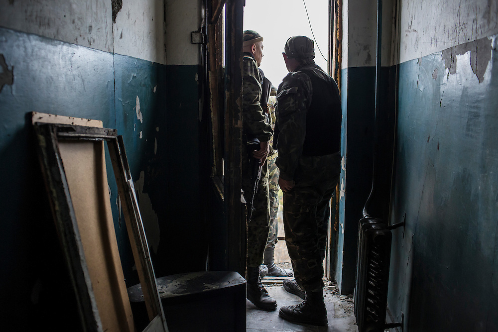 Pro-Russian rebel fighters look out from an apartment building where they can observe and coordinate fighting to gain control of the Donetsk airport on Friday, October 17, 2014 in Donetsk, Ukraine. Photo by Brendan Hoffman, Freelance