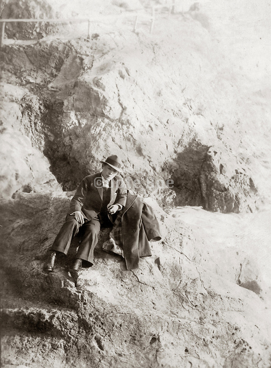 Old photo of a Japanese man sitting on sandy rocks.