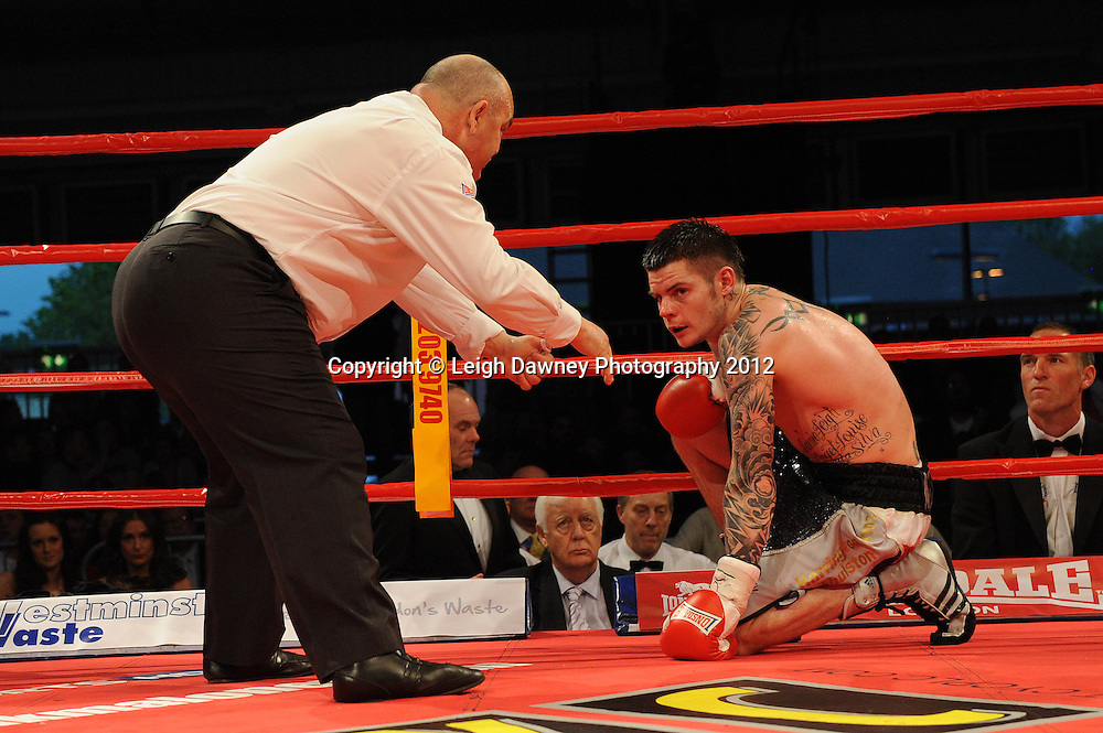 (Referee counts Dave Ryan. Adil Anwar goes onto defeat him in a 10x3 Light Welterweight contest at the Aintree Equestrian Centre, Liverpool on the 19th May 2012. Frank Maloney Promotions © Leigh Dawney Photography 2012.