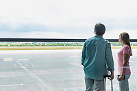 Rear view of mature man looking through the window with his daughter in airport