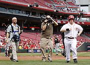 Thursday, April 18, 2013 REDS SPORTS : Cincinnati Reds guest bat boy Teddy Kremer is followed by an ESPN crew, sound guy Chris Bell, left and director of photography and cameraman Ric Hine as they do a special story for the network during their game against the Miami Marlins at Great American Ball Park. The Enquirer/Jeff Swinger