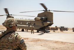 A U.S. Army Soldier, deployed in support of Combined Joint Task Force-Operation Inherent Resolve, waits while a CH-47 Chinook is refueled at Qayyarah West Airfield, Iraq, May 29, 2017. More than 60 Coalition partners have committed themselves to the goal of eliminating the threat posed by ISIS in Iraq and Syria and have contributed in various capacities to the effort. CJTF-OIR is the global Coalition to defeat ISIS in Iraq and Syria. (U.S. Army photo by Cpl. Rachel Diehm)