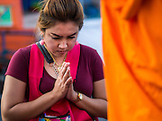 31 MARCH 2015 - BANGKOK, THAILAND: A woman prays after presenting alms to a monk at Wat Benchamabophit in Bangkok. Wat Benchamabophit Dusitvanaram, a Buddhist temple (wat) in the Dusit district of Bangkok, Thailand. Also known as the marble temple, it is one of Bangkok's best known temples and a major tourist attraction. It typifies Bangkok's ornate style of high gables, stepped-out roofs and elaborate finials. Monastic life at Wat Bencha differs from most other temples in that lay people come to the temple to present food and alms to the monks rather than the monks going out and walking through the community as they do at most other Thai temples.     PHOTO BY JACK KURTZ