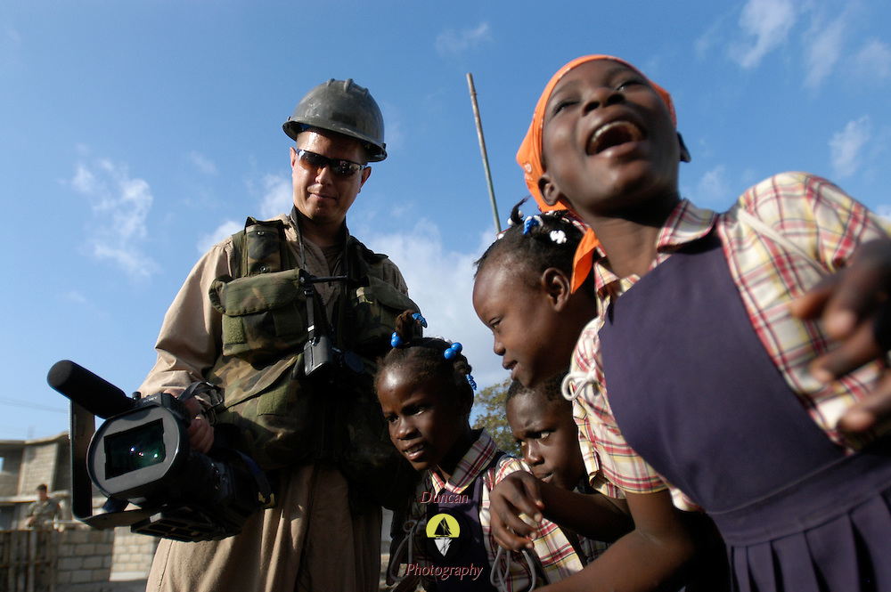 GONAIVES, Haiti (March 10, 2005) -- Navy Chief Journalist (SW/AW) Dave Fliesen (a native of Milwaukee, Wis. and a current resident of Virginia Beach, Va.), left, videotapes the work project at Ecole N.D. de la Nativite, in Gonaives, Haiti.  He turned the viewing screen around backwards so that children from the school could see what he was photographing as it happened.  The U.S. Navy Seabees are constructing a new school building near the site of the school which was damaged in the flooding following the hurricanes of 2004.  Flood waters were more than 12 feet deep at this location.  The U.S. Navy, Army, Marines, Air Force, and Coast Guard are contributing to New Horizons, a three-month humanitarian and civic assistance project in Haiti sponsored by Commander U.S. Southern Command.  The Task Force conducting New Horizons will build three school houses, drill three potable water wells and conduct free health clinics.  U.S. Navy photo by Photographer's Mate 2nd Class Roger S. Duncan, Fleet Combat Camera, Atlantic.