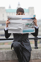 Portrait of a businessman holding newspaper in front of his face with St. Paul's Cathedral in the background
