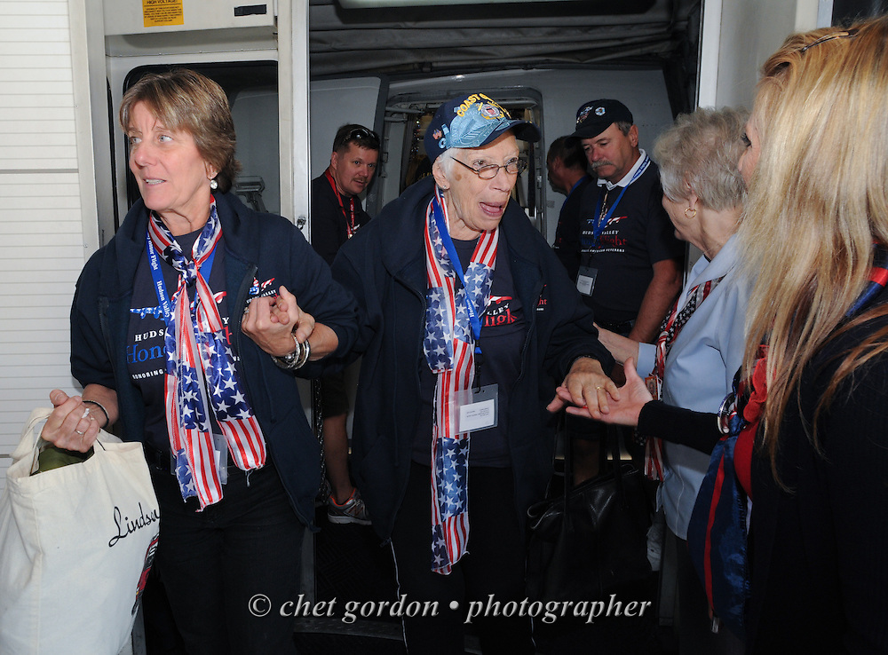 WWII Veterans and their escorts steps off a charter aircraft at Reagan National Airport in Arlington, VA on Saturday, October 18, 2014. Seventy-five WWII Veterans from the Westchester County area toured the WWII Memorial and Arlington National Cemetery onboard the inaugural flight from Westchester County Airport in White Plains, NY. Hudson Valley Honor Flight is a chapter of the Honor Flight Network, which provides free flights for WWII Veterans and tours of the WWII Memorial constructed in their honor, and other sites in the nation's capital.  © www.chetgordon.com