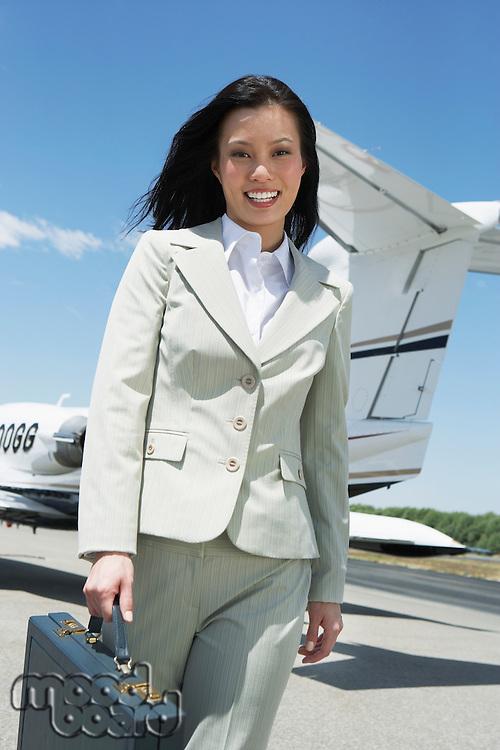 Businesswoman Beside an Airplane