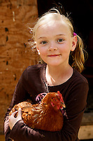 Stella Shern, 8 holds a chicken in front of the coup at Featherdown Farm at the Chaffen Family Orchards near Oroville CA, Saturday April 20, 2013.