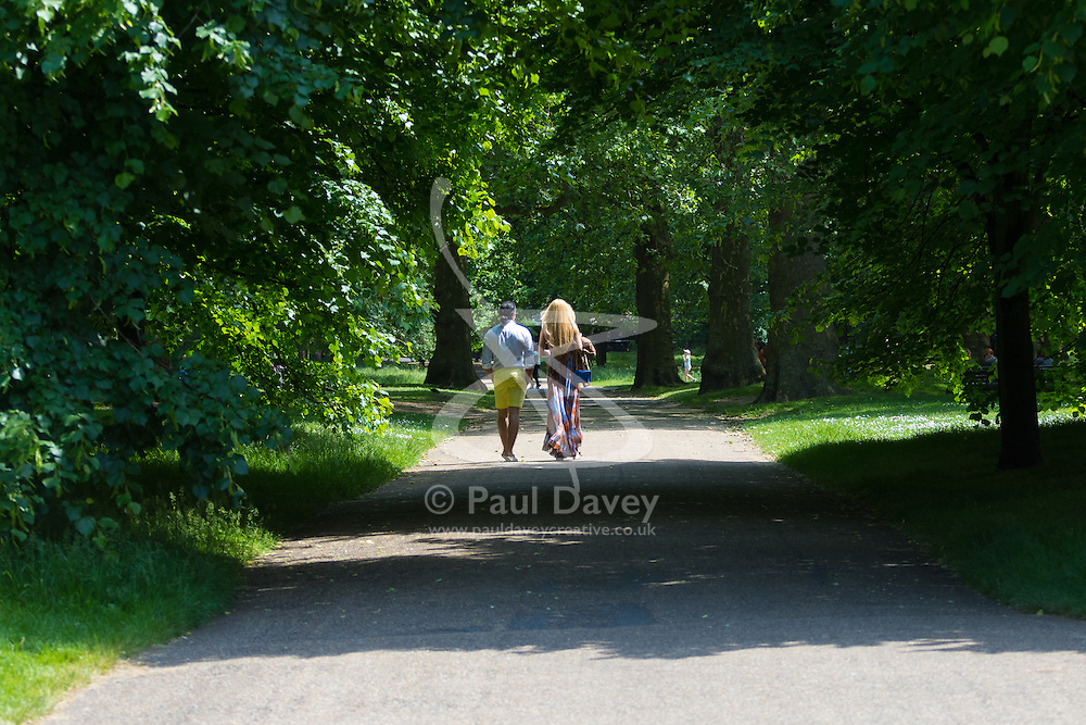 Green Park, London, June 6th 2016. A couple walk through the dappled sunlight in Green Park as London basks in glorious summer sunshine with highs of 24º expected.