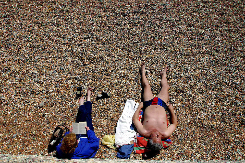 Photo: Mark Chilvers/Insight..Sunbathers take advantage of a rare sunny day on Brighton beach yesterday. 11.07..02..