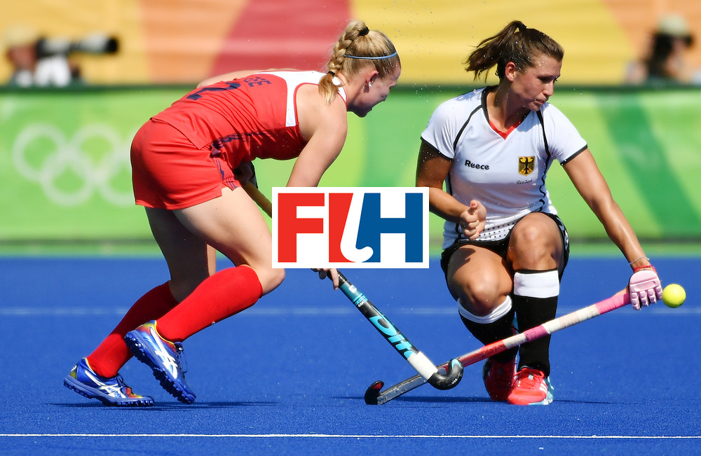 The USA's Stefanie Fee (L) vies with Germany's Julia Muller during the women's quarterfinal field hockey USA vs Germany match of the Rio 2016 Olympics Games at the Olympic Hockey Centre in Rio de Janeiro on August 15, 2016. / AFP / Pascal GUYOT        (Photo credit should read PASCAL GUYOT/AFP/Getty Images)