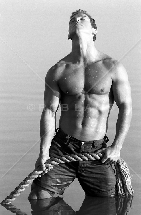 muscular man standing in a lake while pulling a large rope
