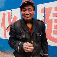 Chongqing - 5 gennaio 2011: un impiegato in un'impresa di costruzioni posa davanti alla camera. Nel 2006 gli investimenti della città in costruzioni e ricostruzione ammontano a 182.221 miliardi di yuan, 26,1% in più rispeto all'anno precedente. Chongqing - January 5, 2011: a construction worker smoking. In 2006 the investment in construction and reconstruction was RMB 182.221 billion, 26.1% higher than the previous year.