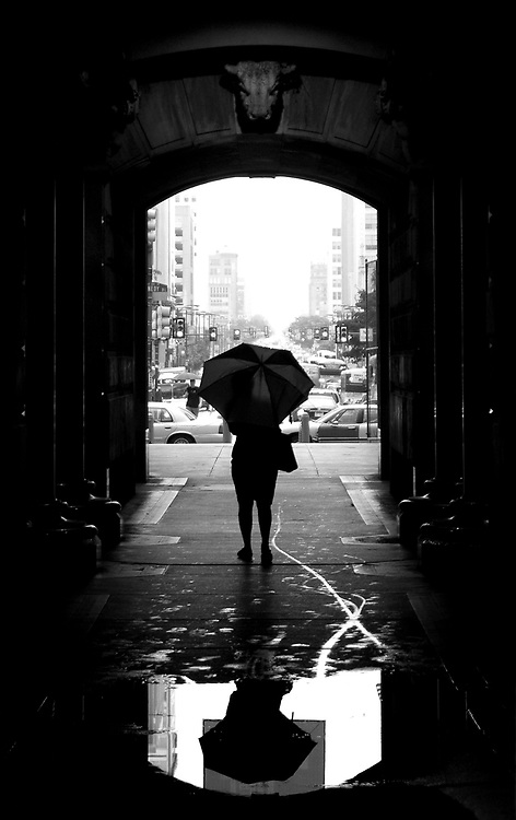 A Center City worker gets a momentary break from heavy rains as she walks through the North Archway of City Hall at the end of the day.