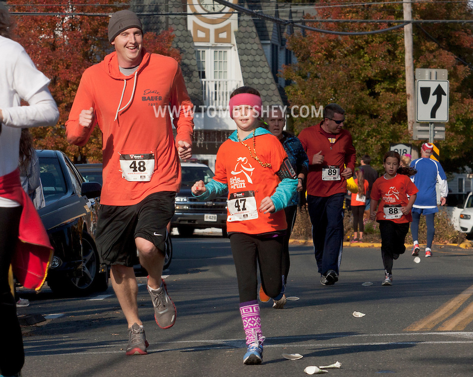Cornwall-on-Hudson, New York - A girl in the Girls on the Run Hudson Valley program and her running buddy approach the finish line at the Cornwall Lions Club Fall Harvest Race 5K on Nov. 10, 2013. Girls on the Run is a national program with a mission of helping girls to be joyful, healthy and confident using an experience-based curriculum which creatively integrates running.