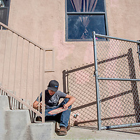 Skills USA participant Austin Jennings touches up a railing with some paint at the Battered Families Services center in Gallup Sunday.