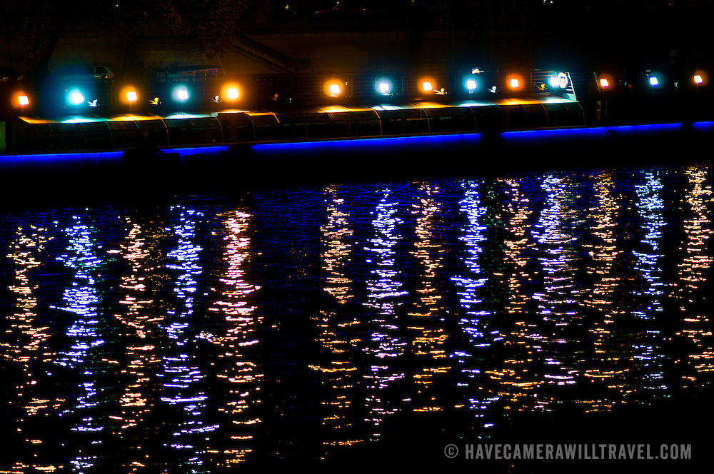 Lights from a passing boat are reflected on the Seine at night in Paris.