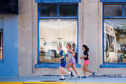 "03 AUGUST 2020 - JEWELL, IOWA:  Girls jog down Main Street in Jewell Monday. The only grocery store in Jewell, a small community in central Iowa, closed in 2019. It served four communities within a 20 mile radius of Jewell. Some of the town's residents created a cooperative to reopen the store. They sold shares to the co-op and  held fundraisers through the spring. Organizers raised about $225,000 and bought the store, which had its ""soft opening"" July 8. The store celebrated its official reopening Monday August 3. Before the reopening, Jewell had been a ""food desert"" for seven months. The USDA defines rural food deserts as having at least 500 people in a census tract living 10 miles from a large grocery store or supermarket. There is a convenience store in Jewell, but it sells mostly heavily processed, unhealthy snack foods that are high in fat, sugar, and salt.        PHOTO BY JACK KURTZ"