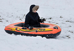 © Licensed to London News Pictures. 01/02/2019. High Wycombe, UK. A boy toboggans in an inflatable dinghy as he enjoys the wintry conditions in High Wycombe, Buckinghamshire after overnight snow falls and continuing low temperatures. Photo credit: Peter Macdiarmid/LNP