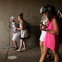 Fans making their way through the infield tunnel stop to watch as an undercard race passes by at the 138th running of the Kentucky Derby at Churchill Downs in Louisville, Ky. Saturday May 5, 2012.  Photo by David Stephenson